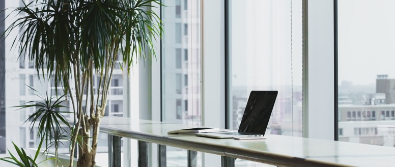 image of laptop on table next to office window